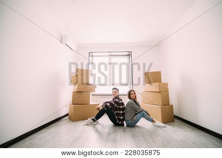 Happy Young Couple Sitting On Floor Near Moving Boxes. Young Family Moving To New Home. Woman And Ma