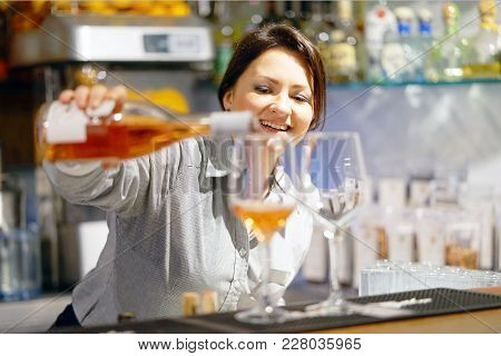 A Barman Girl Standing Smiling, Pours Red Wine Into A Glass From A Bottle. Focus On The Girl