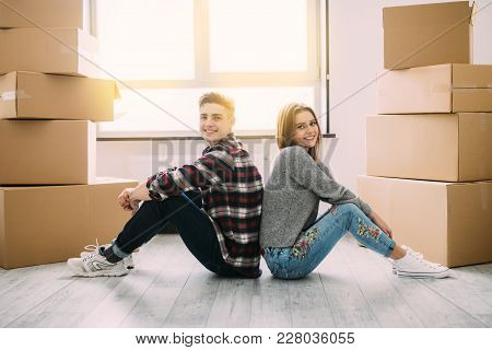 Happy Couple Sitting On Floor Around Boxes After Buying House, Relocation.
