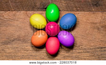 Easter Background With Painted Organic Eggs Arranged In A Flower Shape On Rustic Wooden Table