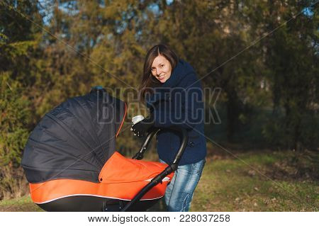 Young Woman In Blue Coat Walking In Autumn Park With Little Child Baby In Orange Baby Carriage, Tea