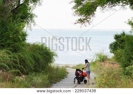 Young Woman Walking At Sea Background With Little Cute Child Baby Boy In Baby Carriage On Nature, Gr