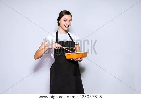Beautiful Young Woman Chef In Black Apron Makes A Delicious Pie