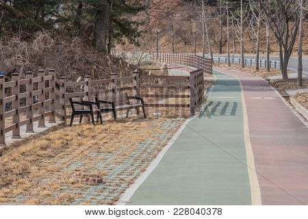 Winter Landscape Of Wooden Park Benches In Front Of Wooden Fence Next To A Public Bike Path