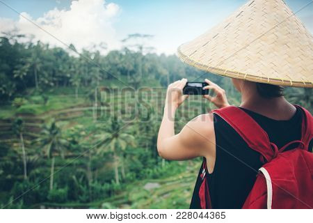 Young Lady With Traditional Asian Hat And Backpack Making A Mobile Photo Of Green Rice Field