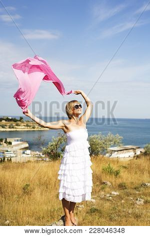 Portrait Of Beautiful Blond Woman In White Dress Standing On Wind With Scarf Near Sea Among Yellow G
