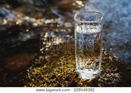 A Transparent Glass With Drinking Mountain Water In Sun Light Stands In The Moss Stone On Sun Beame