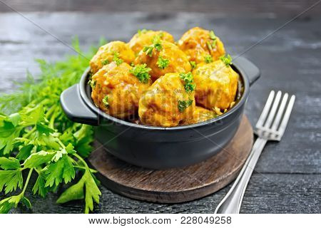 Meatballs With Tomato Sauce In A Brazier, Parsley, Dill And Fork On A Wooden Plank Background