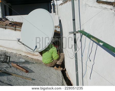 Alora, Spain - November 23, 2011: Man Preparing Walls For Laying Concrete Roof Tiles