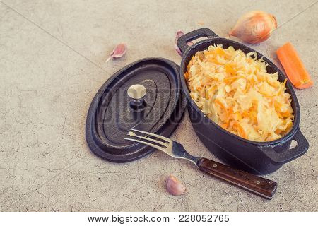Stewed Cabbage In A Black Cast-iron Pot, Next To A Fresh Carrot And Onions On A Gray Background. Veg