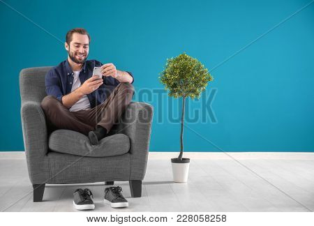 Handsome man with mobile phone sitting in comfortable armchair at home