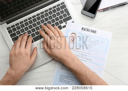 Man with resume form using laptop at table. Job interview concept