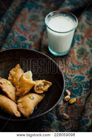 Mawa stuffed Gujiya and flavored glass of milk. Special dessert on the occasion of Holi - a festival of colors.