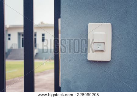 Close Up White Doorbell Or Buzzer Button On Concrete Wall Beside Doorway With House In The Backgroun