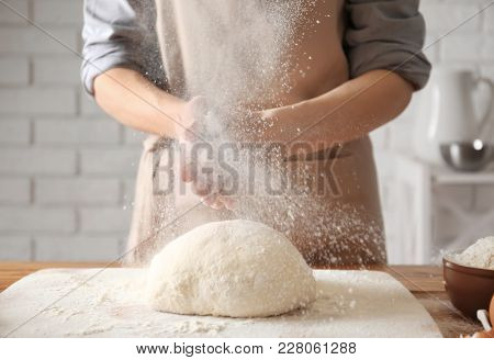 Woman clapping and sprinkling flour over dough on table