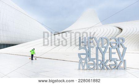 Baku, Azerbaijan - January 01, 2018: Cleaner in bright uniform tidy up teritory of Heydar Aliev Center, Baku, Azerbaijan