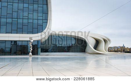 Baku, Azerbaijan - January 01, 2018: Modern wall of glass of Heydar Aliev Center cinstruction building, Baku, Azerbaijan. Silver instalation in front of the wall