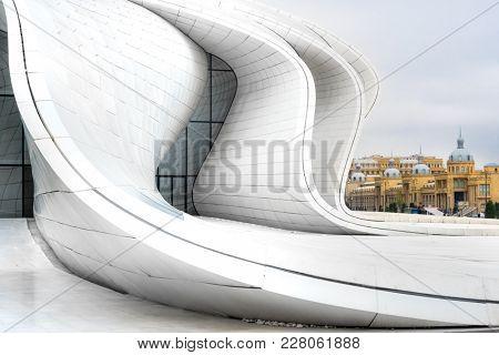 Baku, Azerbaijan - January 01, 2018: White futuristic curved walls of Heydar Aliev Center in Baku with historic buildings, Azerbaijan