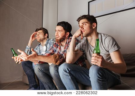 Photo of discontented adult men expressing frustration while sitting on sofa and watching football game in apartment