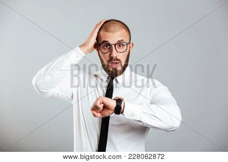 Photo of mature man 30s in business outfit looking on wristwatch and grabbing head isolated over gray background