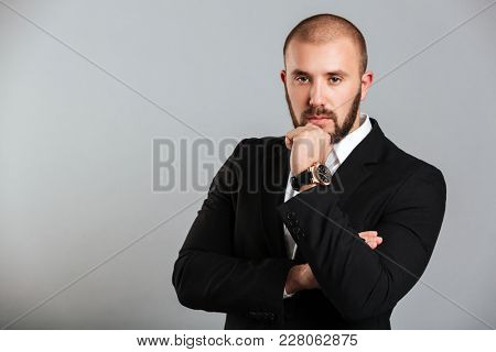 Image of concentrated adult man in black business suit touching his chin and posing with meaningful view isolated over gray background