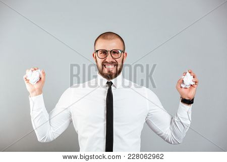Photo of irritated angry businessman in white shirt and eyeglasses crumpling paper documents in both hands isolated over gray background