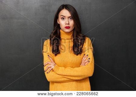 Displeased brunette woman in sweater with crossed arms looking at the camera over black background