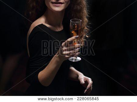 stylish young woman raising a glass of champagne