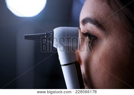 Female doctor using otoscope for examination, side view