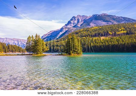 The morning sun warms the lake Two Jack and a small island. Golden Autumn in Canada. The concept of ecological and active touris