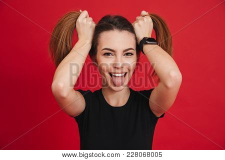 Image of amusing adult girl 20s in black t-shirt playing around and making two ponytails hairstyle with funny face isolated over red background