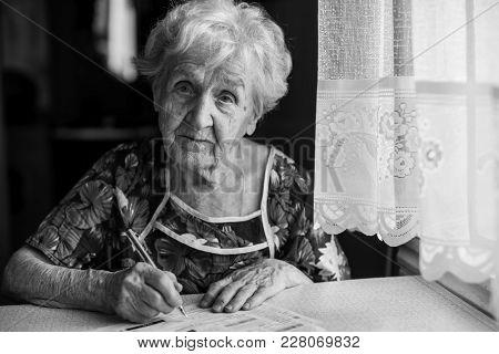 Elderly woman fills out utility bills.