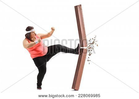 Full length profile shot of an overweight woman kicking a chocolate bar isolated on white background
