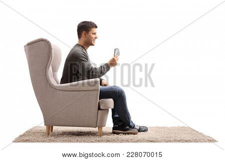 Young man with playing cards sitting in an armchair isolated on white background