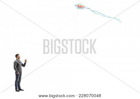 Full length profile shot of a young guy flying a kite isolated on white background