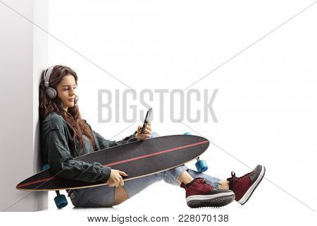Teenage skater girl with a longboard leaning against a wall and listening to music on a phone isolated on white background