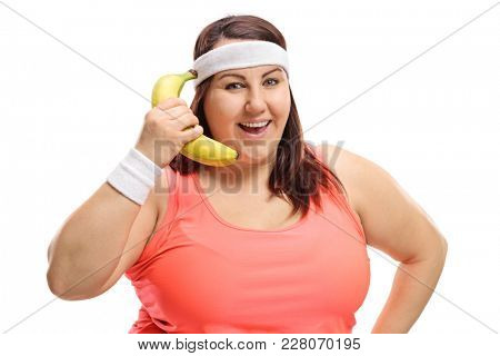 Overweight woman using a banana as a telephone isolated on white background
