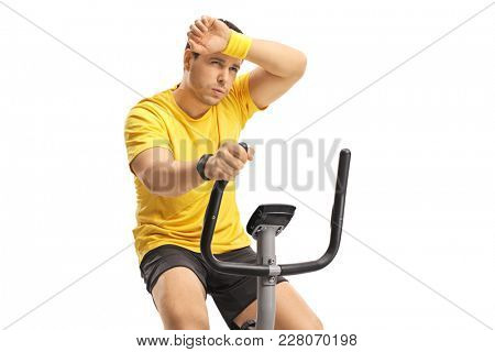 Tired young man exercising on a cross-trainer machine isolated on white background