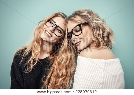 Two pretty girls in glasses are posing in studio over blue background. Beauty, fashion. Optics, eyewear.
