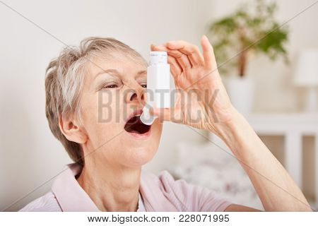 Senior woman holds inhaler for emergency labored breathing