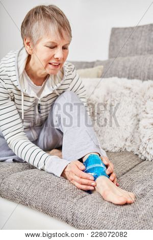 Senior woman with ankle injury cools it with compress