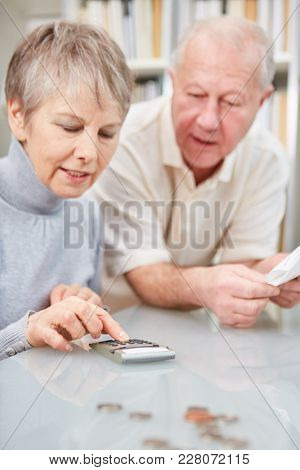 Retiree and pensioner couple doing accounting with calculator