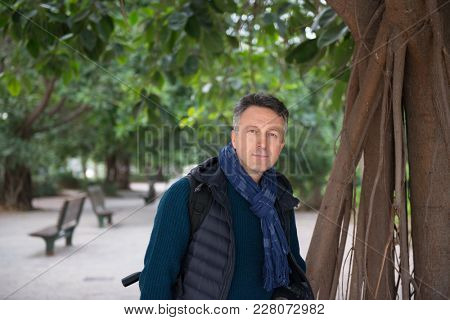 Handsome middle-aged man in Mediterranean park near ficus tree. Attractive mid adult male model posing outddor.