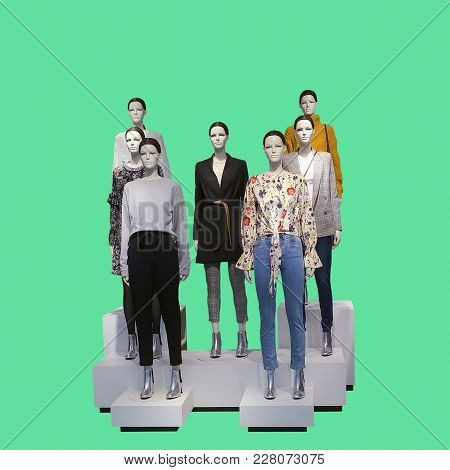Group Of Female Mannequins Wear Fashionable Clothes, Isolated On Green Background. No Brand Names Or