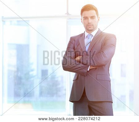 portrait in full growth. confident businessman standing in the spacious lobby