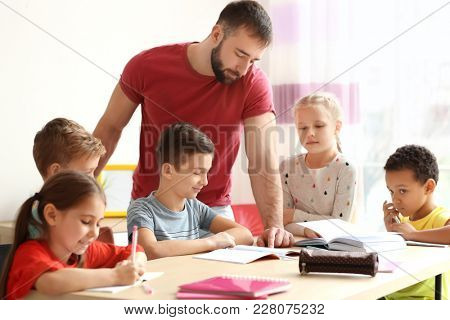 Male teacher helping children with homework in classroom at school