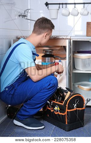 Young plumber repairing sink in kitchen