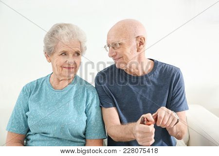 Senior people sitting on couch at home. Elderly care