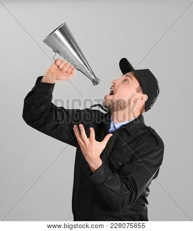 Male security guard with megaphone on grey background