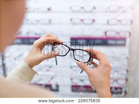 Woman choosing glasses in optician store
